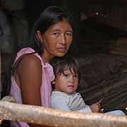 An indigenous woman cradles her young daughter in her log home.