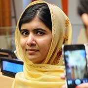 A woman takes a mobile phone photo of education activist Malala Yousafzai, wearing a yellow head covering.