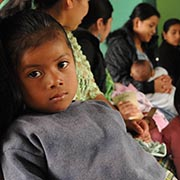 A Mayan girl leans against her mother at a Guatemalan health clinic.