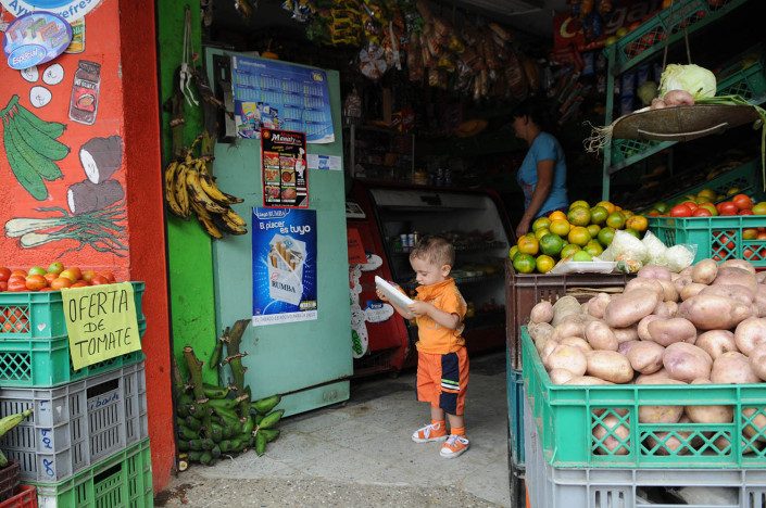 A toddler looks at a package of vegetables in a market in Medellin, Colombia, as his mother shops behind him.