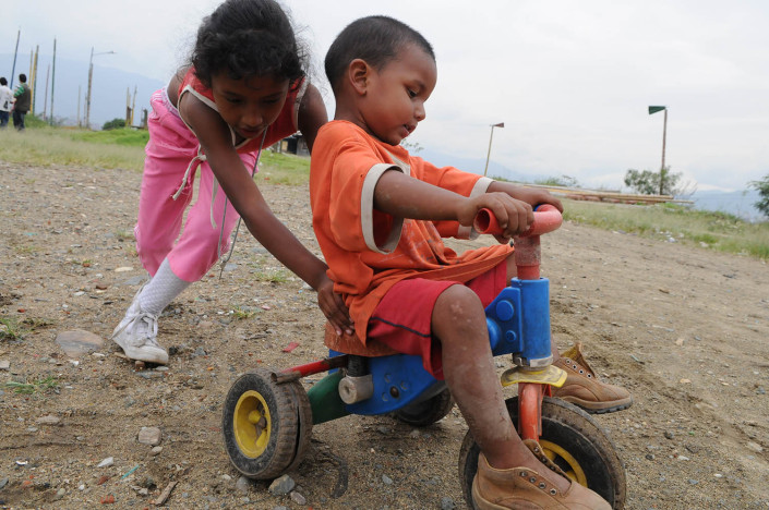 A girl pushes a boy near their homes on a toxic landfill known as El Morro in Medellin, Colombia.