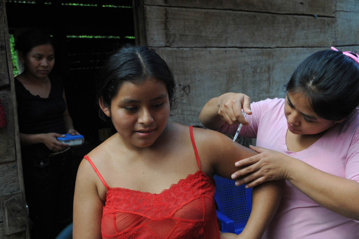 A health worker administers a tetanus vaccine to an indigenous Mayan woman outside her home in rural Guatemala.