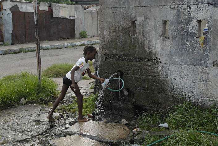 A girl fills a plastic bottle with drinking water at a local water point in Trenchtown in the parish of Kingston and St. Andrew, Jamaica.