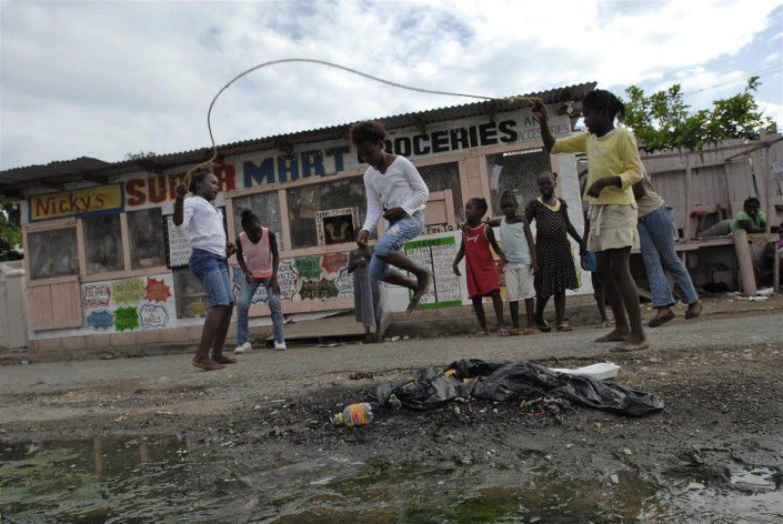 Girls jump rope on a street littered with debris and raw sewage in Trenchtown, in the parish to Kingston and St. Andrew, Jamaica.