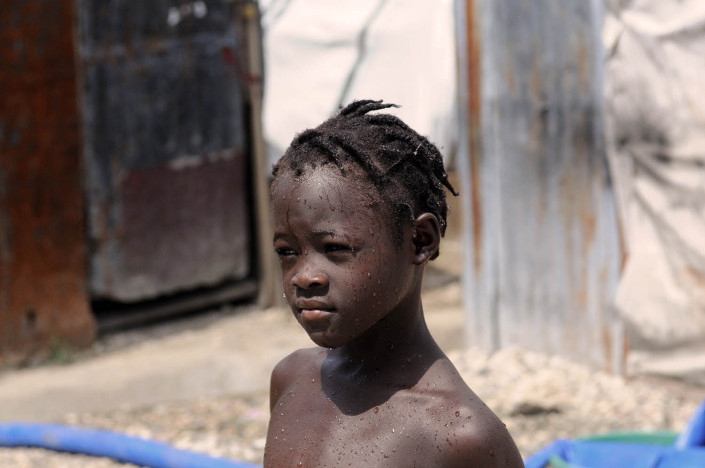 A young girl in Carrefour Aviation, a camp for people displaced by the Haiti earthquake, showers outdoors in Port-au-Prince, Haiti.