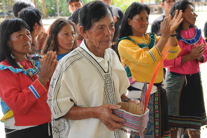 A community leader from the indigenous Shipibo Conibo community of Nuevo Saposoa in the Peruvian Amazon stands with residents, all of whom are wearing traditional dress.