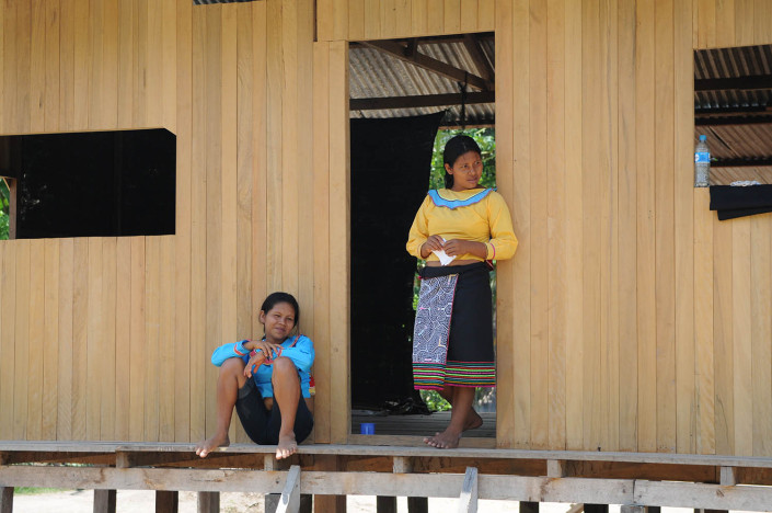 A mother and daughter chat outside their home in the indigenous Shipibo-Conibo community of Nuevo Saposoa in the Peruvian Amazon.