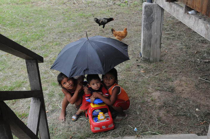Children play with a plastic toy car under an umbrella outside their home in the indigenous Shipibo-Conibo community of Nuevo Saposoa in the Peruvian Amazon.