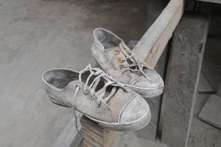 A pair of well-worn sneakers sit on a wooden beam of a wooden house in the indigenous Shipibo-Conibo community of Nuevo Saposoa in the Peruvian Amazon.