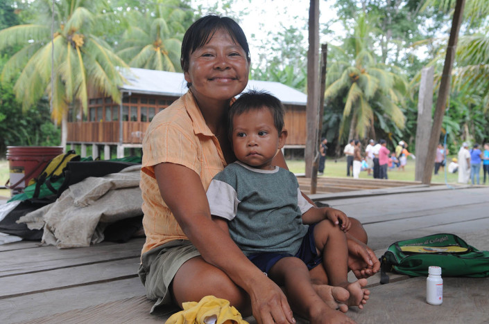 A mother smiles holding her young on her lap inside their home in the indigenous Shipibo Conibo community of Nuevo Saposoa in the Peruvian Amazon.