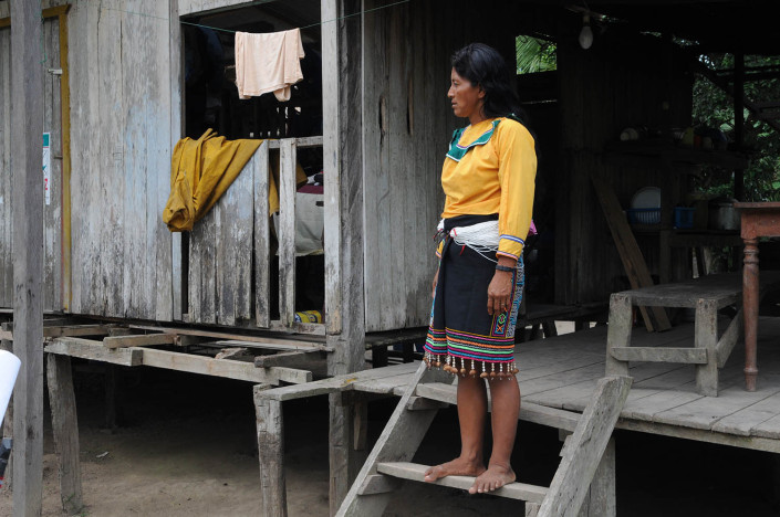 A woman wearing traditional dress, stands on the wooden steps of her home in the indigenous Shipibo-Conibo community of Nuevo Saposoa in the Peruvian Amazon.