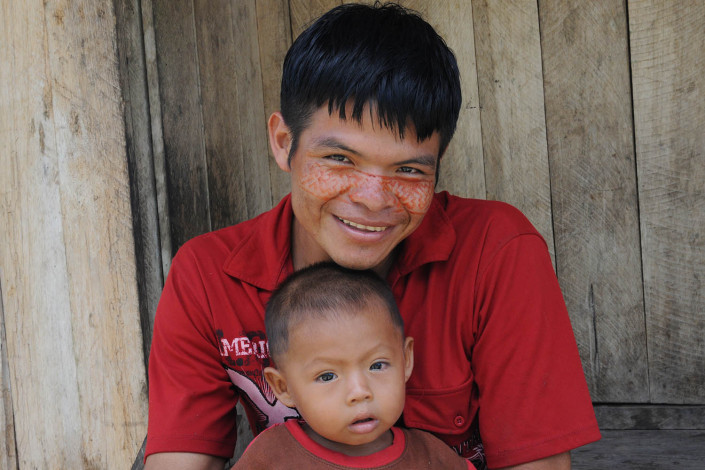 A father wearing paint on his face, and his son, sit outside their home in the indigenous Shipibo-Conibo community of Nuevo Saposoa in the Peruvian Amazon.