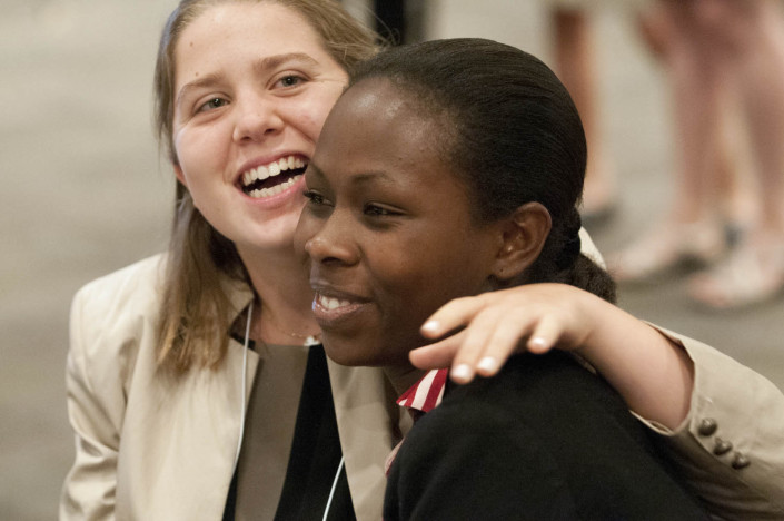 Two young women embrace at a disabilities conference.