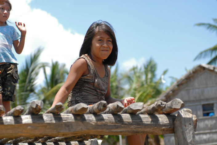 A smiling indigenous Anu girl sits on a wooden dock outside her home above the water, in Laguna de Sinamaica, Venezuela.