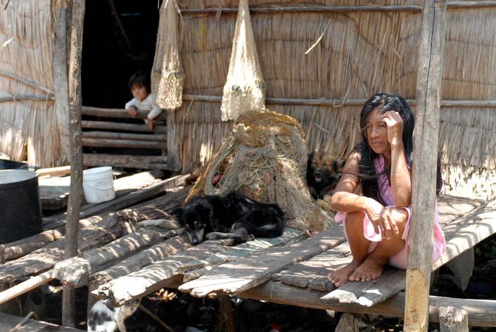 An indigenous Anu woman sits on a makeshift wooden dock outside her home above a lagoon as dogs laze nearby and her daughter leans out of a window, in Laguna de Sinamaica, Venezuela.