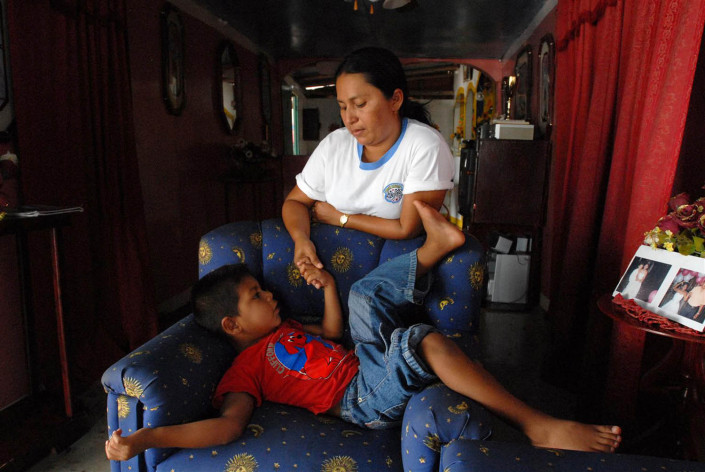 A 5-year-old Anu boy holds his mother's hand, as he tells her a traditional story in their home in Laguna de Sinamaica, Venezuela.