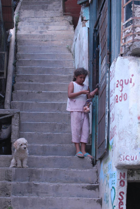 A girl buys eggs from a street vendor, from a shop along a steep concrete staircase, as a small dog watches nearby, in a poor neighborhood of Caracas, Venezuela.