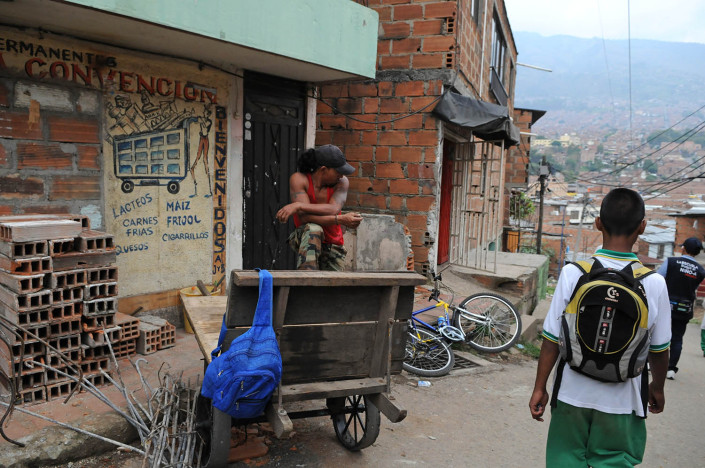 An adolescent boy walks home from school in a city in Colombia.