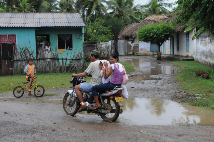 A couple with their child on a motorcycle on a flooded rural street in northern Colombia.