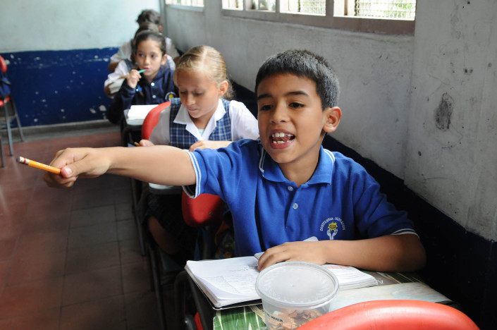 A boy raises his hand during a Spanish class in Medellín, Colombia.