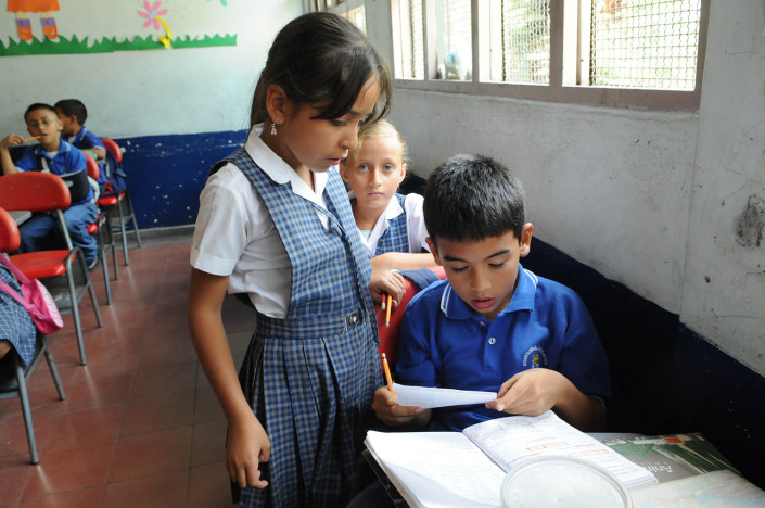 A girl helps a boy in Spanish class in Medellín