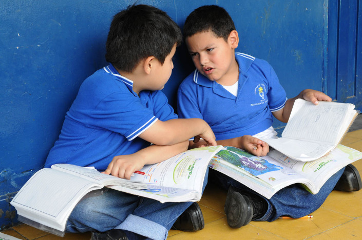 Boys sitting on the floor, discuss their schoolwork at a school in Medellín, Colombia.