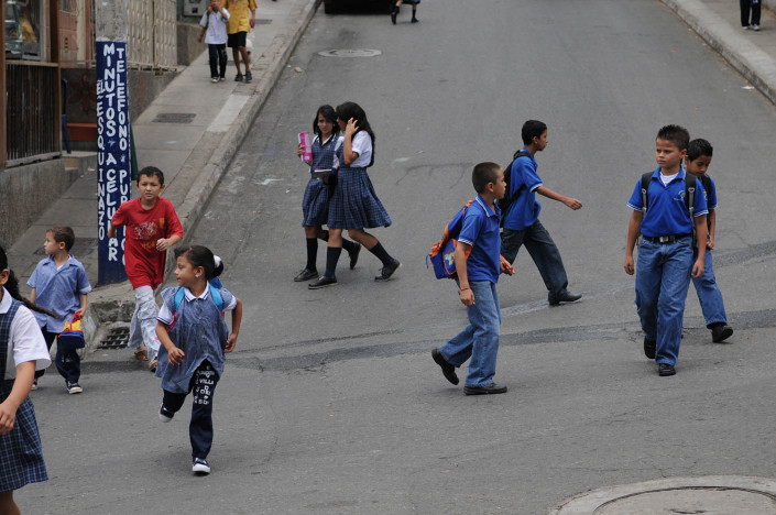 Children cross the street on their way home from school in Medellín, Colombia.
