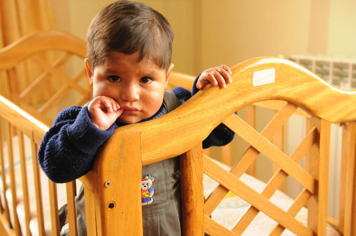 A toddler stands in a crib at a shelter in Potosí, Bolivia.