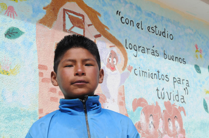 Roberto, 11, sands in front of a mural at the Roberto School in the city of Potosí, Bolivia.