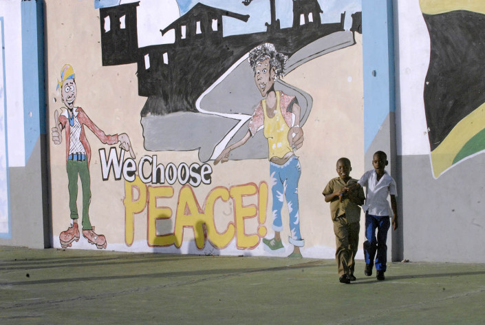 "Children walk outside a painted mural that says ""Peace Initiative."""
