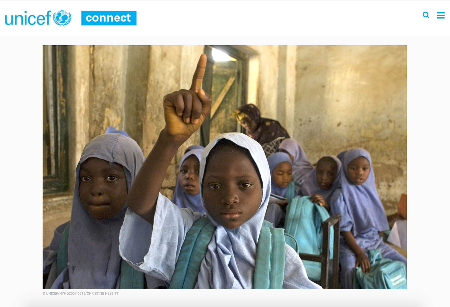 Screen capture showing a photograph of Nigerian schoolgirls, one raising her hand in the foreground.