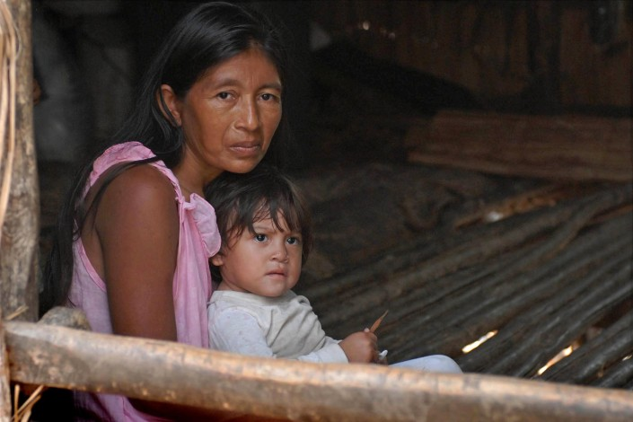 A woman sits with her 1-yearpold in her home made of wooden poles, above a lagoon, in Venezuela.