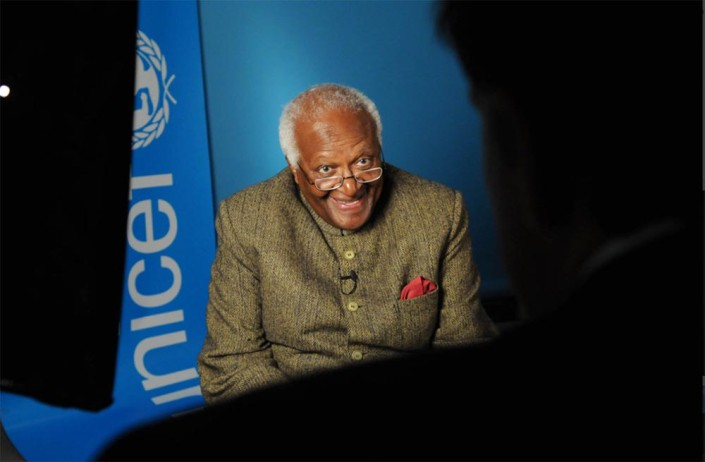 Archbishop Desmond Tutu, smiling broadly, is interviewed in a studio with a UNICEF logo in the background.