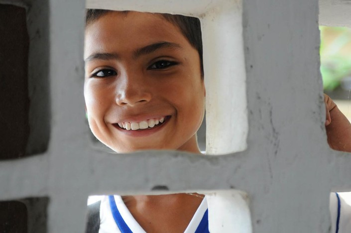 A smiling boy boy looks through a white cement block window into his classroom in Colombia.