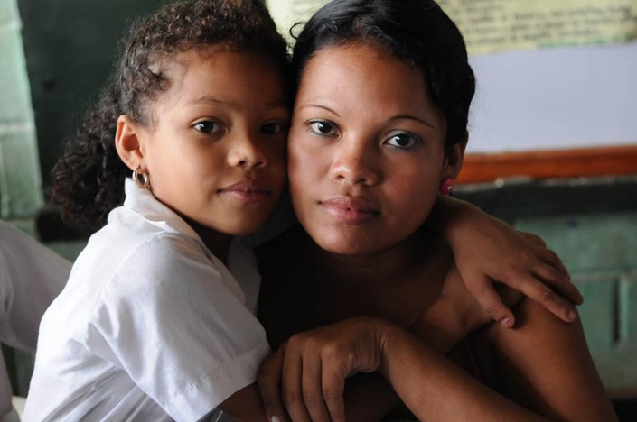 A girl and her mother lovingly embrace during a school activity in Colombia.