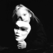 A pensive 7-year-old girl holds a mask in her hand, mirroring the look on her face, in a studio portrait.