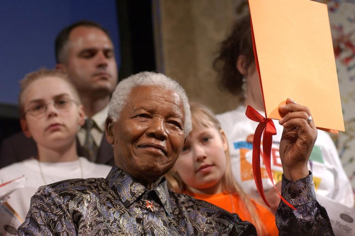 A smiling former President of South Africa Nelson Mandela holds a folder of stories of children from around the world.