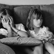 7-year-old cousins in their pajamas, sit together on a sofa the morning after a sleepover.