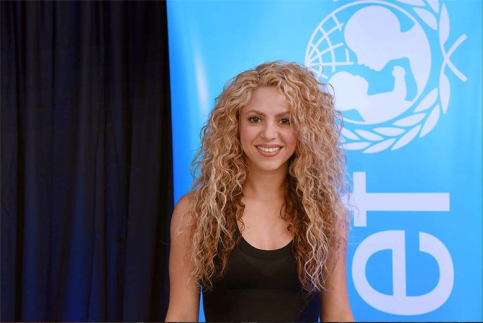 UNICEF Goodwill Ambassador and internationally renowned singer songwriter Shakira stands in front of a banner with a UNICEF logo in an official portrait.