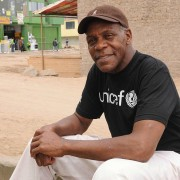 Actor Danny Glover, wearing a UNICEF t-shirt and brown cap, smiles as he sits outside a UNICEF supported childcare center in Lima, Peru.