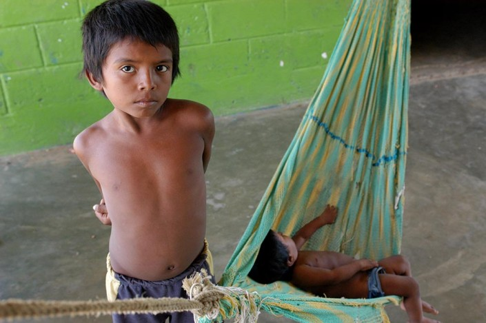 Wilmer, an 8-year-old boy, watches over his baby brother, asleep in a hammock in a community center in Paraguaipoa, Venezuela.