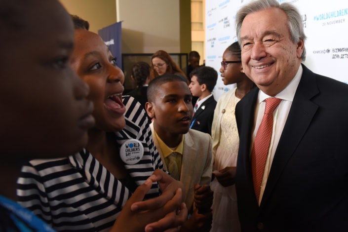 UN Secretary-General António Guterres speaks with smiling adolescent activists at the UN.