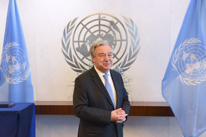 UN Secretary General Antonio Guterres stands in his conference room in front of the UN logo and between UN flags