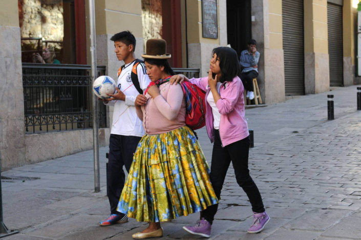 A woman in indigenous dress with her two modern-dressed adolescent children in La Paz, Bolivia.