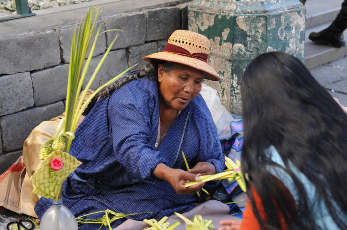 A woman wearing a straw hat sells decorative palm fronts in the shape of crosses on a street in Bolivia.