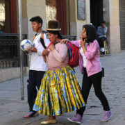 A Bolivian woman wearing a traditional bowler hat and traditional skirt, walk with her son and daughter, in contemporary clothing, along Calle Sacarnaga in La Paz, Bolivia.